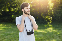 Portrait of stylish bearded man with retro camera standing at green park looking into distance with thoughtful expression. Young m Stock Images