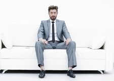 Successful businessman sitting in a suit smokes. Portrait of a stylish bearded man in white shirt on leather sofa Royalty Free Stock Photography