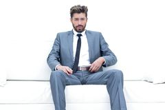 Successful businessman sitting in a suit smokes. Portrait of a stylish bearded man in white shirt on leather sofa Royalty Free Stock Image