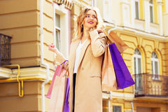 Portrait of stylish, beautiful blonde hair smiling girl with shoppings. Happy shopping. Royalty Free Stock Photography