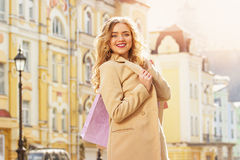 Portrait of stylish, beautiful blonde hair smiling girl with shoppings. Happy shopping. Royalty Free Stock Photo