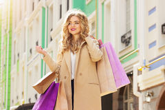 Portrait of stylish, beautiful blonde hair smiling girl with shoppings. Happy shopping. Stock Photos