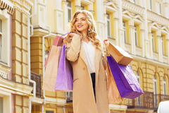Portrait of stylish, beautiful blonde hair smiling girl with shoppings. Happy shopping. Royalty Free Stock Photos