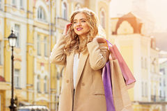 Portrait of stylish, beautiful blonde hair smiling girl with shoppings. Happy shopping. Stock Image