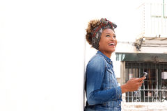 Stylish black female standing outdoors with smart phone Stock Photography