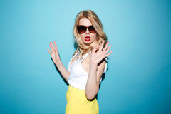 Portrait of a stylish blonde woman wearing sunglasses and posing. Portrait of a beautiful stylish blonde woman wearing sunglasses and posing isolated over blue Stock Photos