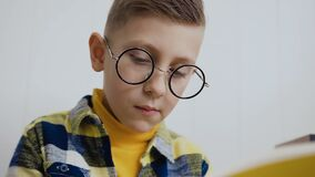 Portrait of a stylish boy who wears round glasses and makes notes in a notebook. Close-up, beautiful boy in glasses has. Copybook. The stylish blonde, little stock footage