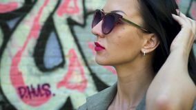 Portrait of stylish brunette in sunglasses touching her hair. Stylish brunette in sunglasses and with red lipstick is posing for camera against graffiti wall stock video