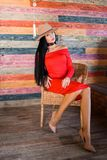 Portrait of a stylish brunette woman wearing a red dress, beige shoes and hat and sitting on a chair royalty free stock photos