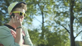 Portrait of a stylish cheerful boy talking on phone, outdoors. stock video