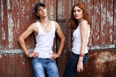 Portrait of a stylish couple in jeans standing near wooden house Stock Photography