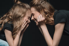 Portrait of stylish daughter and mother smiling, touching foreheads and looking at each other stock images