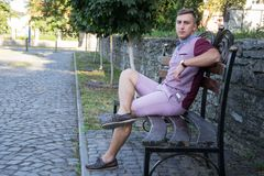 Portrait of stylish fashionable american man sitting at park on bench Royalty Free Stock Photography