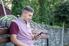 Portrait of stylish fashionable american man sitting at park on bench and watch mobile phone Royalty Free Stock Image