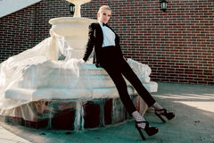 Portrait of stylish fashionable beautiful blonde woman in man black suit with bow Royalty Free Stock Image