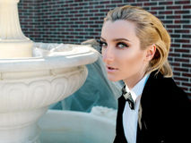 Portrait of stylish fashionable beautiful blonde woman in man black suit with bow Royalty Free Stock Photos