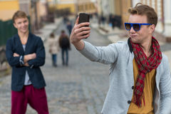 Portrait of stylish fashionable young man staying on the street Royalty Free Stock Photo