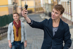 Portrait of stylish fashionable young man staying on the street Stock Image