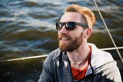 Portrait of a stylish fisher man driving a motor boat in sunset time. Portrait of a stylish fisher man driving a motor boat in sunset time stock photo