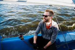 Portrait of a stylish fisher man driving a motor boat in sunset time. Portrait of a stylish fisher man driving a motor boat in sunset time stock photography