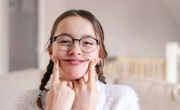 Portrait of stylish foolish attractive smiling preteen girl in glasses with pigtails making artificial smile by fingers on her ch stock photo