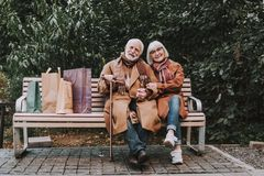 Beautiful elderly couple sitting on bench with shopping bags royalty free stock image