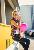 Portrait of stylish girl in eyeglasses and hat posing with ballo Royalty Free Stock Photography
