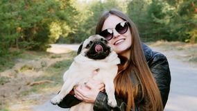 Portrait of stylish girl hug caress funny pug dog in the park in slow motion. Holds on hands stock video