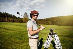 Portrait of stylish golfer in glasses standing on golf course wi stock photo