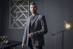 Portrait of stylish handsome business man in luxury apartment. Businessman in dark interior. man in fashionable business. Gray suit in house. wine on table and royalty free stock photography