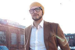 Portrait of stylish handsome young man in glasses with bristle standing outdoors. Man wearing jacket and shirt. stock photos