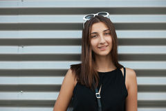 Portrait of stylish happy young beautiful hipster woman against metal urban background Royalty Free Stock Photography