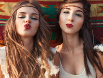 Portrait of Stylish hippie girls having fun and send kiss over e. Tnhic background. Boho casual style Stock Photos