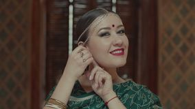 Portrait of stylish indian woman putting earrings. Portrait of attractive female putting massive golden earrings and charmingly smiling. Confident in her beauty stock video footage