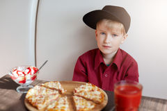 A portrait of stylish little boy dressed in red shirt and modern cap sitting at table in the cafe tasting delicious pizza, ice-cre royalty free stock images