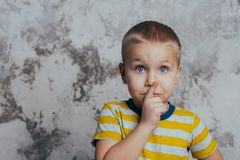 Portrait of a stylish little boy with a finger up near his lips stock photography