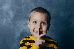 Portrait of a stylish little boy with a finger up near his lips royalty free stock photography