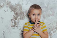 Portrait of a stylish little boy with a finger up near his lips royalty free stock photo