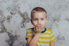 Portrait of a stylish little boy with a hand near his lips sends a kiss royalty free stock image