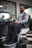 A portrait of a stylish man on barbershop background. Handsome guy with a new haircut. Style, fashion concept. A full-length portrait of a handsome stylish royalty free stock photography