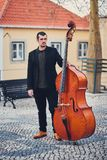 Portrait of a stylish man with a beard on an old street with a double bass. A solid musician with a large musical instrument in br. Own leather shoes, a shirt Stock Photography