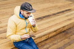 Portrait of stylish man with beard wearing cap, yellow jacket and jeans drinking delicious coffee and listening to music with earp. Hones holding mobile phone royalty free stock photography