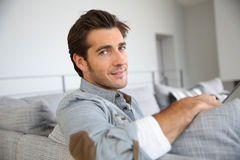 Portrait of stylish man relaxing on sofa Stock Photography
