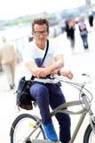 Portrait of stylish man riding city bike Stock Images
