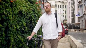 Portrait of stylish man walking to work with bicycle. Portrait of stylish young man walking to work with bicycle Royalty Free Stock Photos