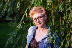 Portrait of stylish  middle aged woman smiling on the nature bac Stock Images