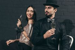 Portrait of stylish multicultural couple with glasses of champagne. At christmas party stock image