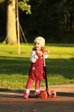 Portrait of a stylish one year old girl riding a scooter on a lovely sunlit summer day. In the park Royalty Free Stock Photography