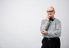 Portrait of stylish pensive senior. Portrait of elegant retired man in striped shirt with bow tie holding his hand on chin and looking at camera thoughtfully Royalty Free Stock Photo