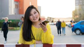 Stylish Pan-Asian girl posing outdoor. Portrait of stylish plus size pan-asian girl using voice recognition of smartphone. Woman is smiling and looking at camera stock photography